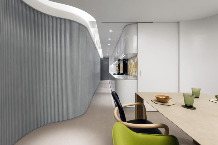 A narrow hallway through the kitchen moves the eye along the glossy finish of the white cabinets, contrasting the paneled wall opposite the kitchen. Neutral colors within the backsplash complements the modern-styled furniture, unifying the dining room and kitchen.