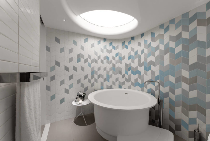 The center of the bathroom features one of three circling artificial skylights that casts down onto the stand-alone white bathtub. The colors on the tile wall depleting as they move towards the entryway.