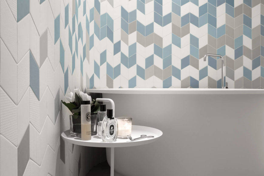 The bathtub sits like a sculpture, sweeping edges complementing the looping of the walls. The curved wall laced in gradient of blue hexagonal Mutina wall tiles.