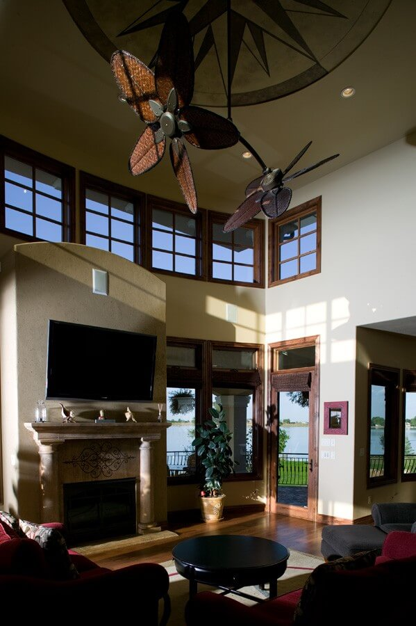 The home's great room features windows that look out on the wraparound porch and the lake. The focal point of the seating area is the screened fireplace topped by a large television. At the top of the room is a custom photo ceiling with two ceiling fans.