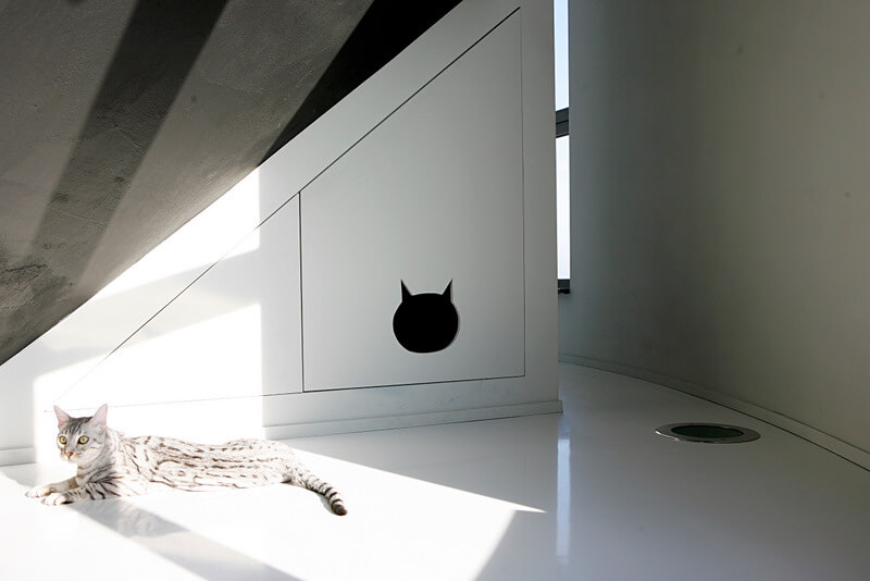 A small nook behind one of the staircases is fitted with a small hole in the door in the shape of a cat's head. The litter box is neatly contained behind this door, which opens for easy cleaning.