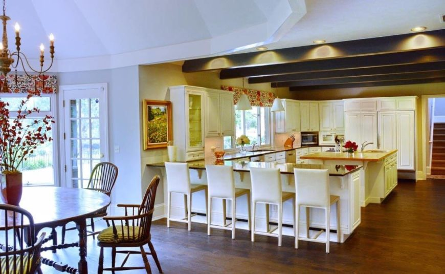 The kitchen itself is a massive open-plan design, with sleek countertops and exposed overhead beams defining the cooking area. An array of white bar stools sits at the close countertop, allowing for ample dining space.