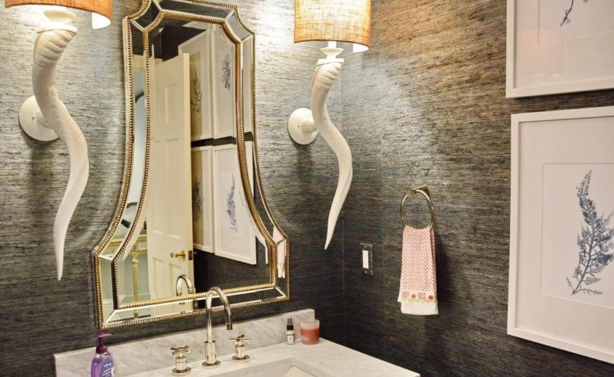 One of the bathrooms features a pair of painted horn sconces flanking a bell-shaped mirror. Marble vanity stands in contrast with slate grey walls.
