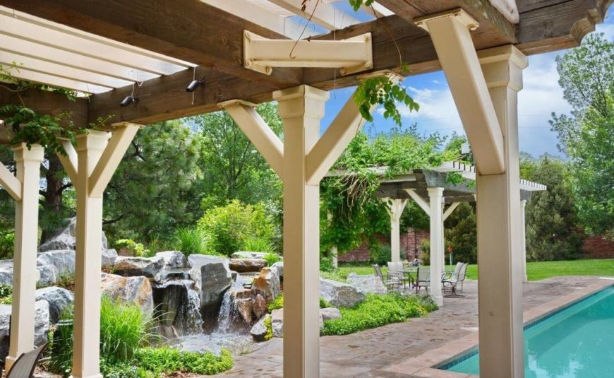 The back yard is an oasis of large stones, moving water features, and a large swimming pool at right. The partially sheltered patio holds abundant space for dining and relaxing furniture.