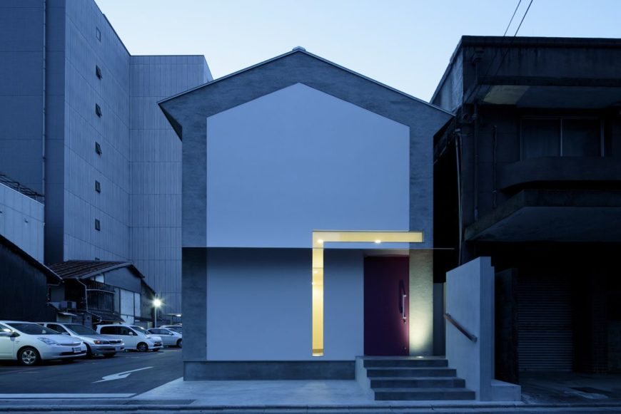 """Returning to the exterior of the home, we see it glowing at night from within, via the L-shaped """"key"""" window. The small footprint and minimalist style of this home helps it stand apart in a crowded neighborhood."""