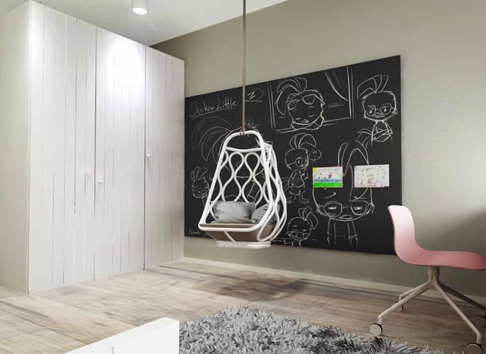 A storage closet is built-out from the wall. Next to it is a large chalkboard and a hanging reading chair.
