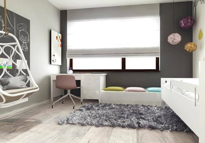From this angle we can see the large window on the dark gray accent wall. A small white desk and a low-profile window bench sit along the wall, with a plush gray area rug nearby.