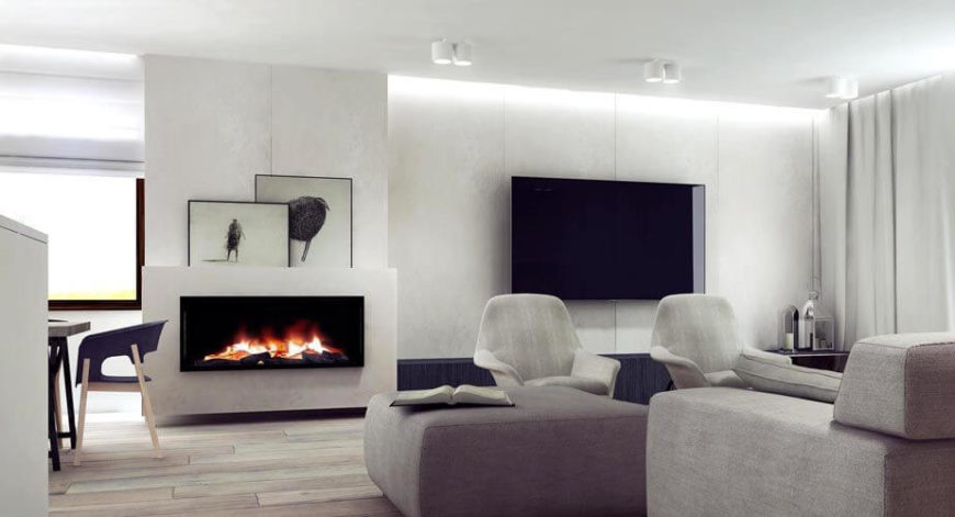 Back in the main living area of the kitchen, dining room, and living room is the small seating area that features a large fireplace and a wall-mounted television. The colors of the formal living room are muted, like those in the adjacent kitchen and dining room.
