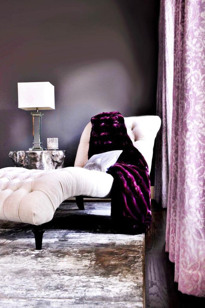 A close up on the chaise lounge and the curtains covering the windows reveals another layering of texture. A shimmering sequined throw pillow rests on the chaise lounge, while a crystalline votive holder sits nearby on the nightstand.