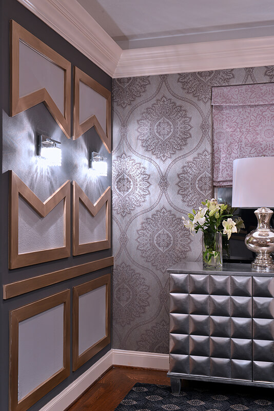 Dividing the room's walls between decorative panelling and wallpaper is a clever trick to keep the patterns from feeling overwhelming when paired with the luxurious carpet. The dresser is metallics and is topped by a chrome table lamp and a glass vase full of lilies.