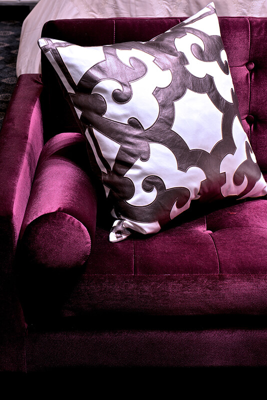 A detailed look at the jewel-toned velvet sofa in a rich wine color. A throw pillow in white with faux leather accents in a dark burgundy adds depth of color and texture.