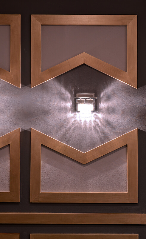 Envelope-shaped wall panels surround the simple wall sconces. In addition to the trio of chandeliers, these wall sconces provide enough light for the owners to party all night.