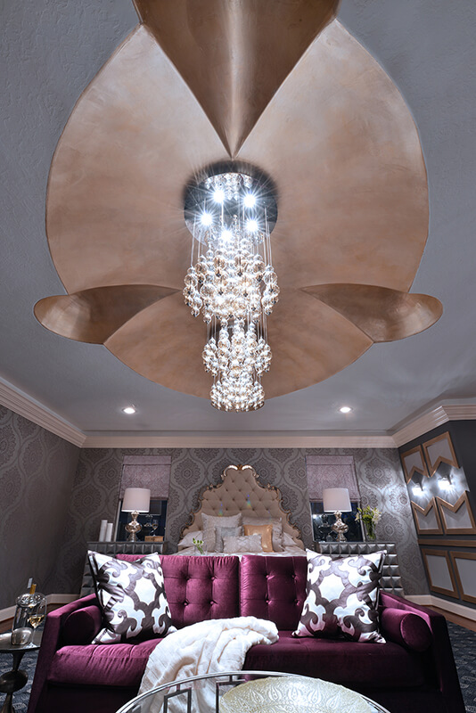 This shot looking upwards towards the trio of chandeliers reveals the incredible custom ceiling details in brown and bronze. This unique tray ceiling adds a level of grandeur to the room that a flat ceiling never could.