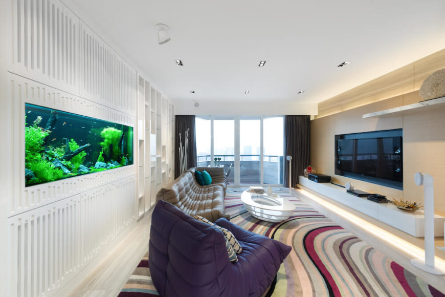 A large aquarium is built directly in the wall, which is slitted in a very interesting manor. Though the floor is covered in a pale hardwood flooring, a large sweeping rug full of beautiful colors is centered in the communal area.