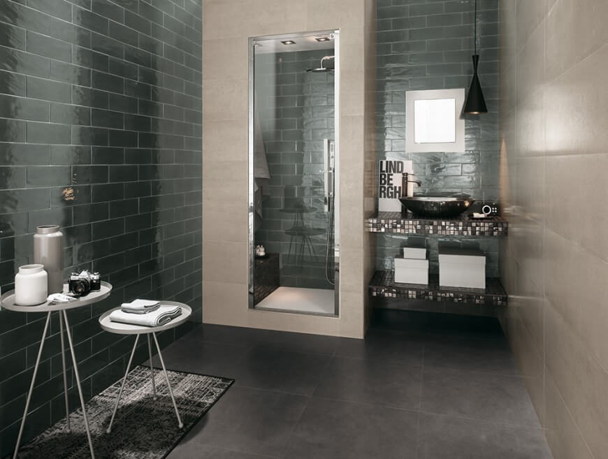 This lovely space has a shower encased by tile and a glass door. The vanity is delicately tiled with a small square window letting in just enough light for a soft white glow.