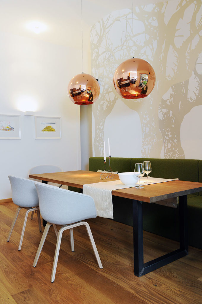 The dining room sees the large natural wood table flanked by contemporary white curved chairs on one side, and green bench seating on the other. Above, a pair of copper globe lights hang.