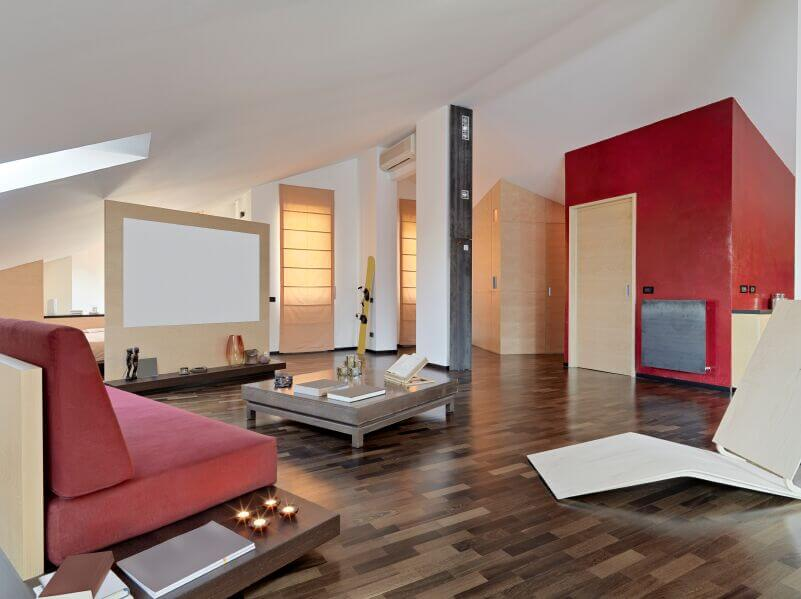 A Beautiful Open Concept Living Room With Multi Tonal Wood Floors And A  Rich Red