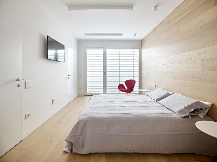 The bedroom maintains the minimal decor and neutral color scheme of the rest of the house creating a calming, relaxing spot. The windows lead out to one of the smaller loggias.