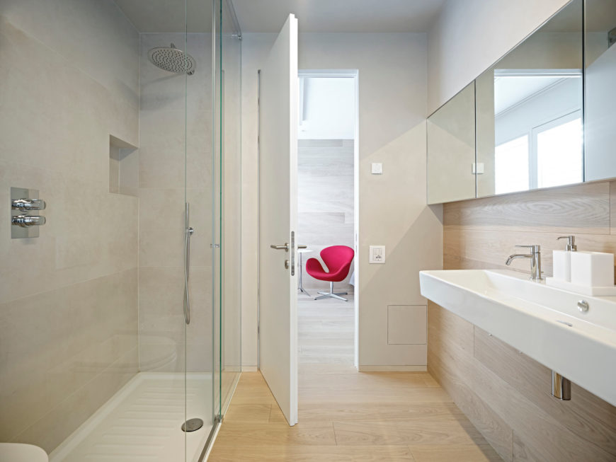 The first of two bathrooms features a shower and large sink area in light, airy colors; allowing for the space to feel bigger while remaining small but functional.