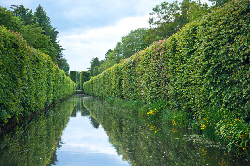 This attractive waterway, bordered by tall, imposing hedges, provides an added sense of calm to the scene.