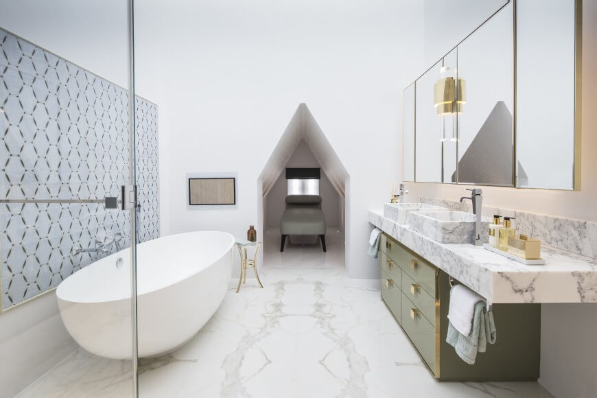 This striking bathroom is full of soft light. The marble floor moves all the way to a small resting nook at the end of the bathroom.