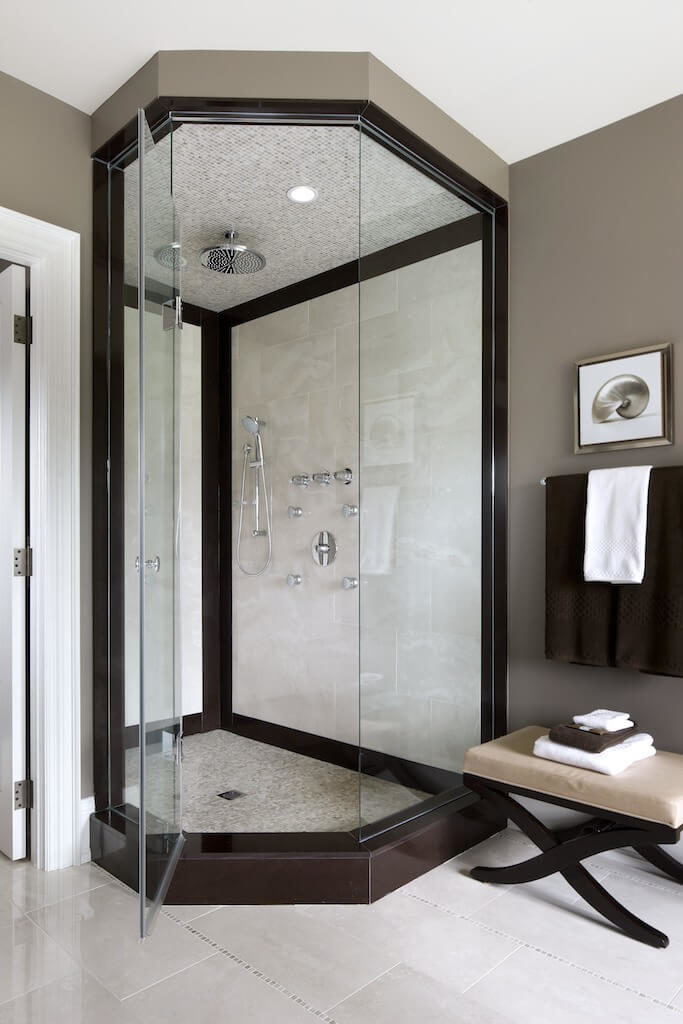 The same bathroom has an glass enclosed shower with an uncommon shape to it. The corner shower is encased with a dark wooden perimeter.
