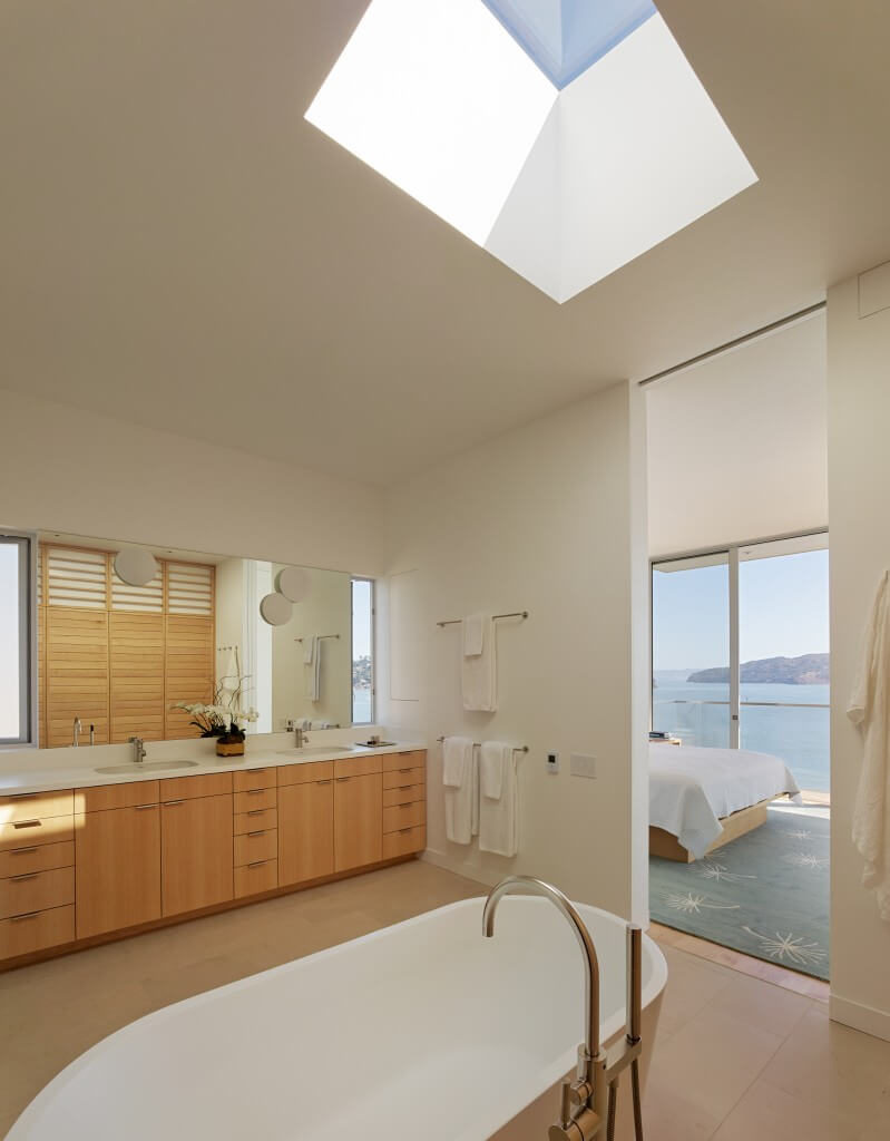 This space using a lot of light toned natural wood. The bathroom is connected directly to the bedroom and has a large skylight for plenty of natural light.