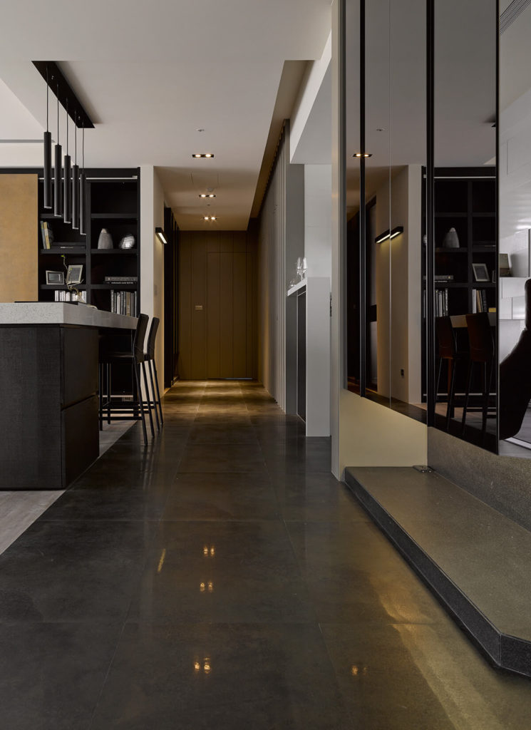 The hallway gleams with large format tile flooring, a glossy contrast to the textural wood tones seen throughout most of the home.