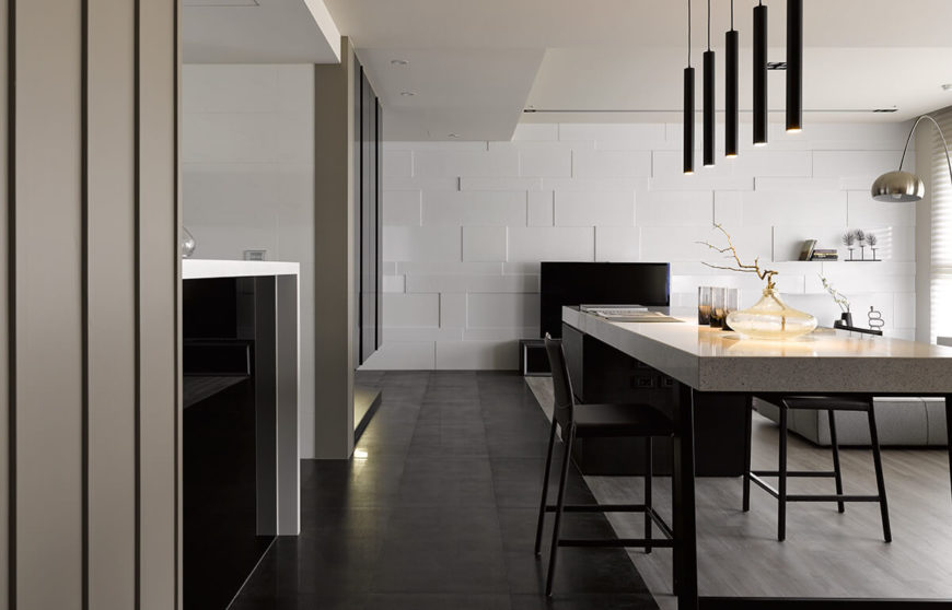 The kitchen countertop extends into the gap between spaces, helping define the hallway itself. At the far end we see the distinct geometric patterns on the end wall.