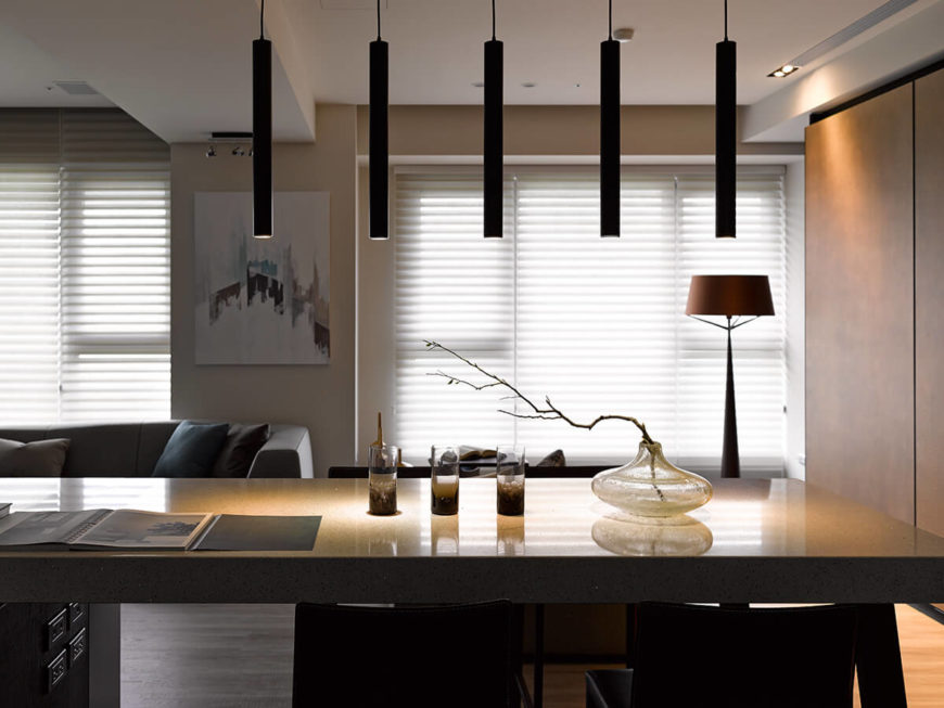 The set of five thin cylindrical pendant lights is one of many innovative lighting elements that aim to underscore the highly functional modern nature of this home design.