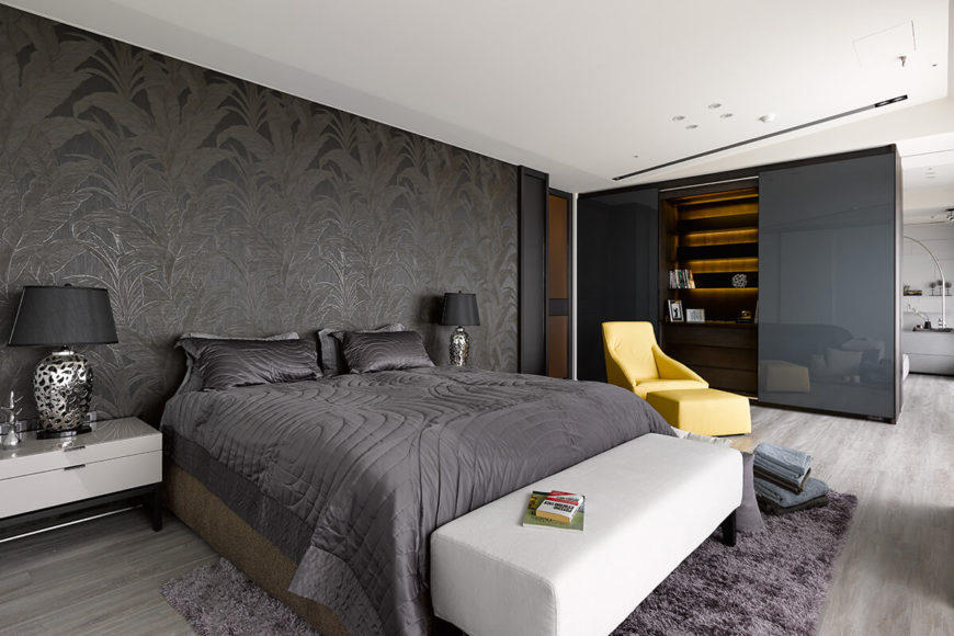 The bedroom is a veritable rainbow of color compared to the rest of the home, punctuated by a soft yellow recliner and ottoman. Dark, textured wallpaper contrasts with light hardwood flooring.