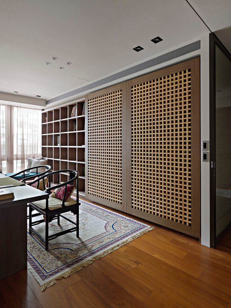 Built into the wall is a room-size cubic shelving system, fitted with a pair of large sliding panels to obscure the storage when not in use.