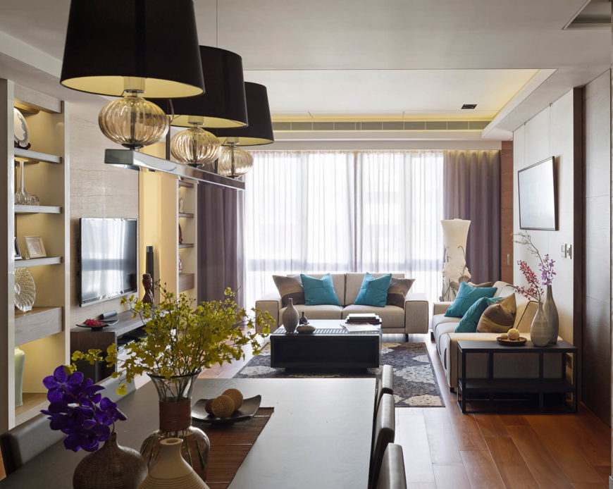 The living and dining room spaces are separated only by the expanse of rich hardwood flooring. The dining table and chairs feature a similarly minimalist, contemporary look as the living room set.