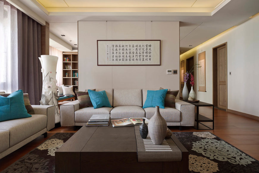 The central, light hued wall dividing the living room and home office is a free standing structural element, offering a mental divide without completely separating the spaces. The sleek, contemporary furniture highlights the unfussy design philosophy.
