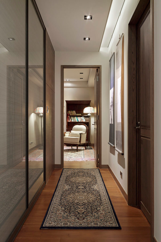 Moving down the central hallway, we see a cozy bedroom opened at the far end, with a more traditionally styled armchair at center. Wall art and a simple area rug add texture and detail to the space.