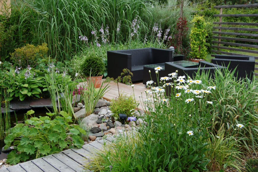 If you thought contemporary was only for the inside of the home, you were mistaken! The black wicker furniture in this beautiful garden brings a deep modern contrast to the lively greens.