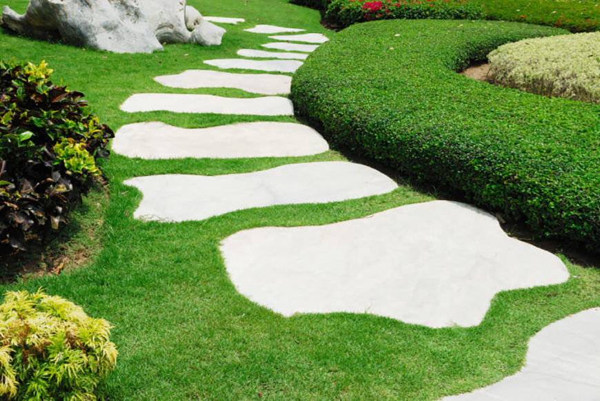 This walkway has marble slabs in whimsical shapes leading through the green grass. The walkway is located in a very open space for a sunlit path.