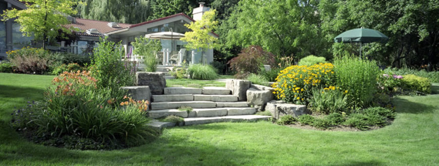 A gorgeous stone walkway leads up towards the patio and pool area. Two large areas on either side are full of bright and beautiful flowers.