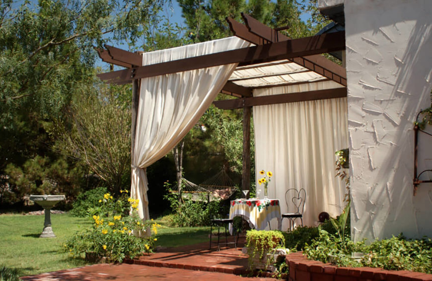 This yard is equipped with a gorgeous patio with a beautiful view of the open yard. Large cream colored curtains hang over the patio for that elegant look.