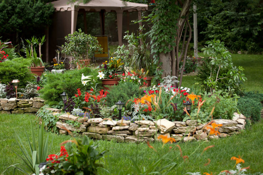 The flowers used in this garden are lovely and exotic while the stacked stone wall adds a rustic, homey quality to the landscaping.