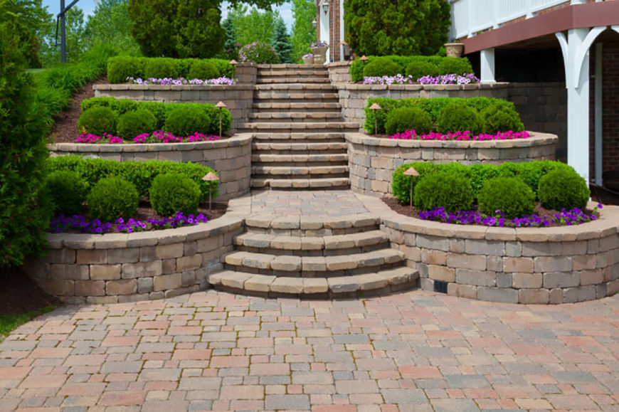 This bricked patio is reminiscent of the entrance to a large estate. The contrast of the rich green foliage and the brightly colored flowers in a lovely addition.
