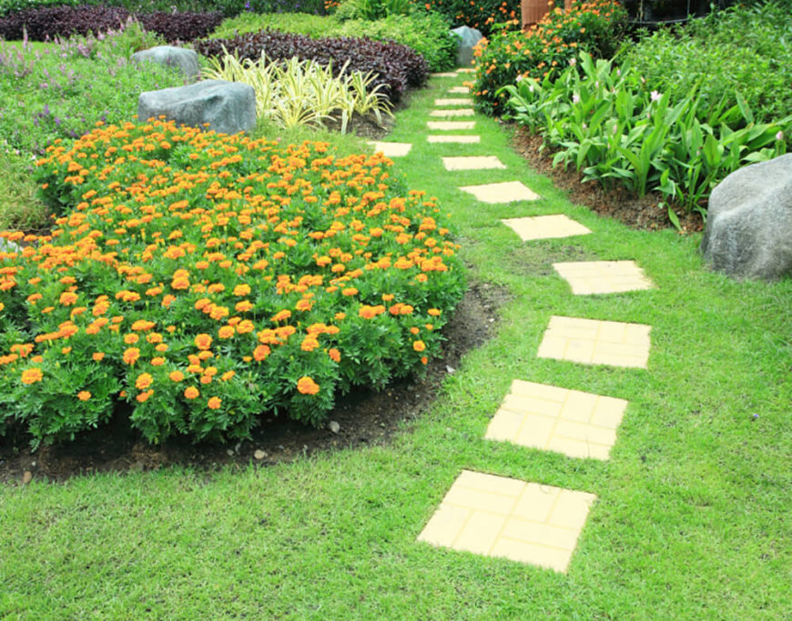 The winding path of this lushly planted garden makes a bright statement against the green of the grass.