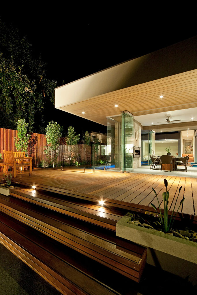 Before saying goodbye, we return to the expansive and rich wood patio. The intricate lighting within and without the home helps to highlight the entire package, landscape and all.