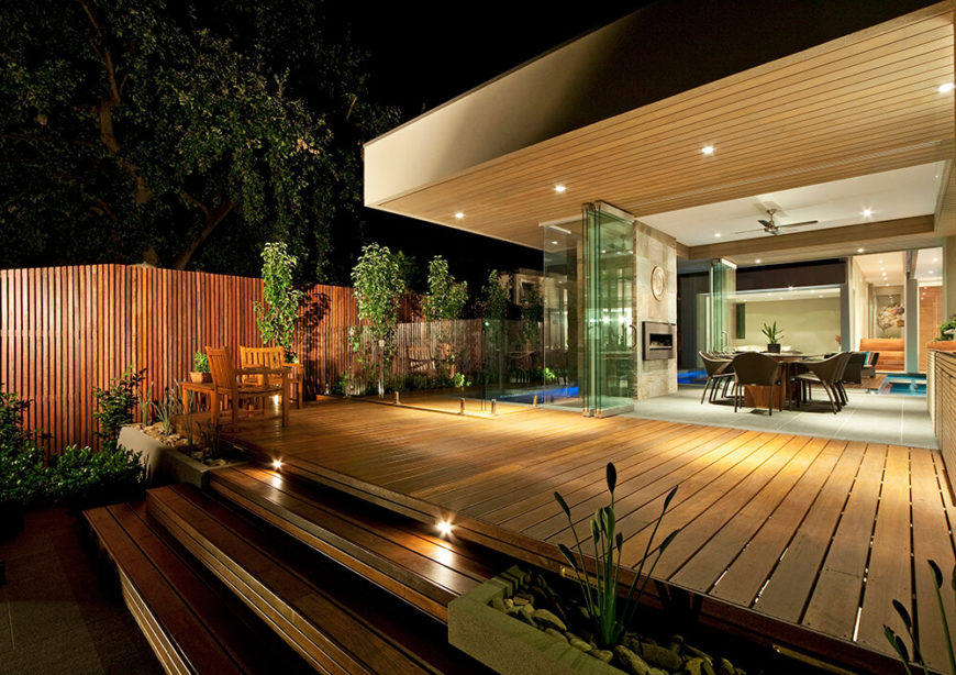 Glancing across the rich hardwood patio at night, we can see deep into the home thanks to both the open-plan design and expanse of retractible glass panels. The intention is to thoroughly blur the line between indoors and out.