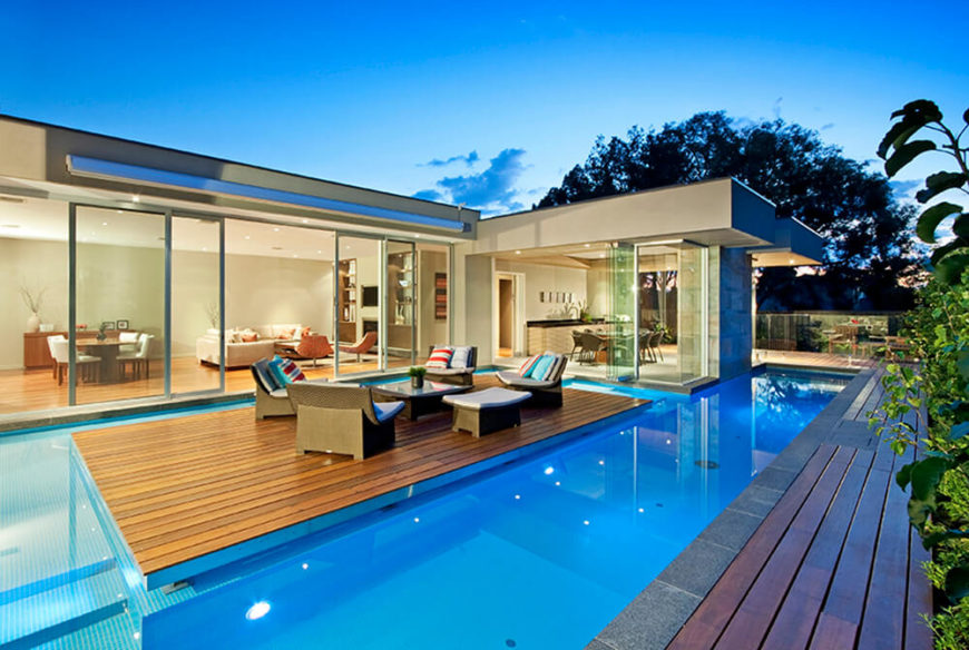 """Moving around the side of the home, we see the """"floating"""" patio section, completely detached from the home by a slim channel of water. A set of relaxing rattan furniture makes this a prime social space."""