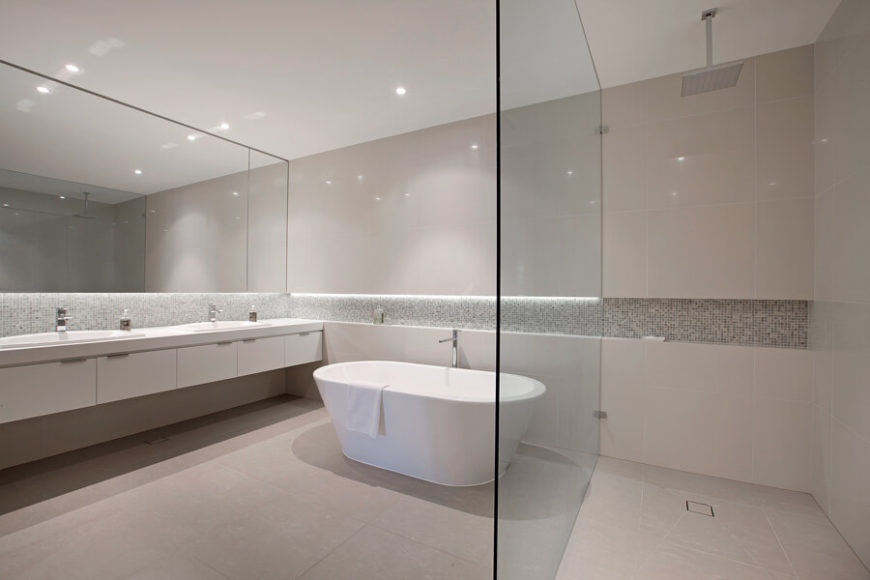 The master bathroom is an expansive, open space with a large walk-in shower divided by glass, and a white soaking tub at center. The dual vanity runs the length of the room with sleek white cabinetry.