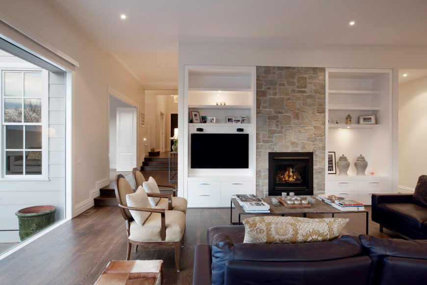 Right around the corner, we see the living room awash in natural light via full height glazing at left. The stone wrapped fireplace stands flanked by built-in shelving, while the hardwood floor supports a set of contemporary furniture.