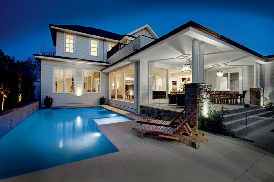 The pool stands tightly hugging the home itself, with an integrated jacuzzi at center. The patio is divided from the raised, sheltered portion by frameless glass edging.