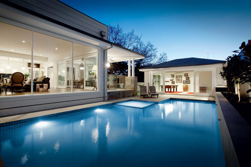 Across from the home itself is this beautifully open pool house, replete with sliding glass doors for a design that integrates the outdoors.