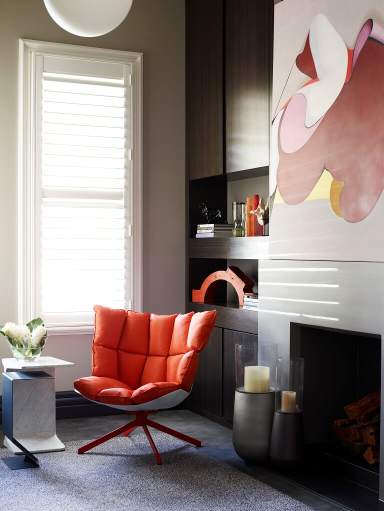 This cozy home office space features another subtle burst of color, with a plush modern orange chair adding a hint of playfulness to the stately, neutral toned room. A fireplace at right is topped by a colorful painting, with rich wood shelving filling out the corner.